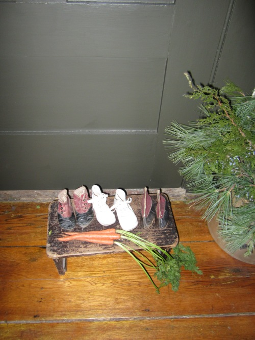 Tiny shoes wait by the door for Saint Nicholas, along with carrots for his horse.