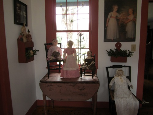 One of my reproduction Izannah Walker dolls sits on a 19th century drop leaf table, with early salmon paint, along side 19th and early 20th century cloth dolls.  C. 1830-1840 milliners models fill the hanging box at the left.