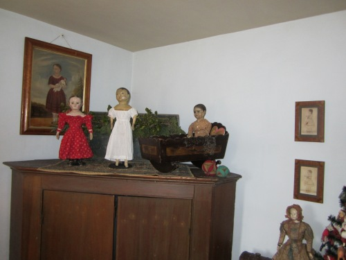 Three of my antique Izannah Walker dolls on top of a large corner cupboard that conceals a TV.