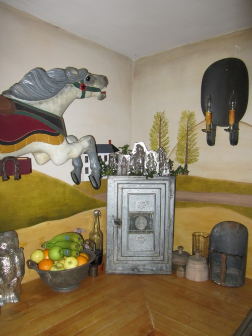A child size C.W. Parker carousel horse that we restored gallops across the Rufus Porter style mural that I painted in the kitchen.