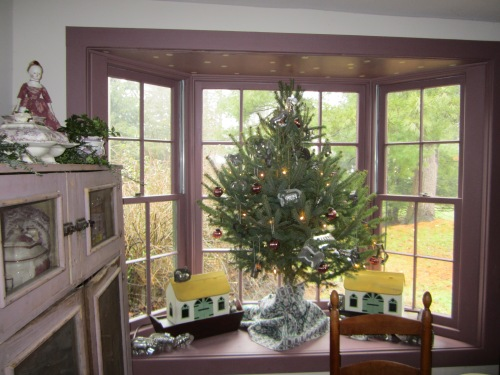 A small Christmas tree graces the bay window in our 1840's kitchen.