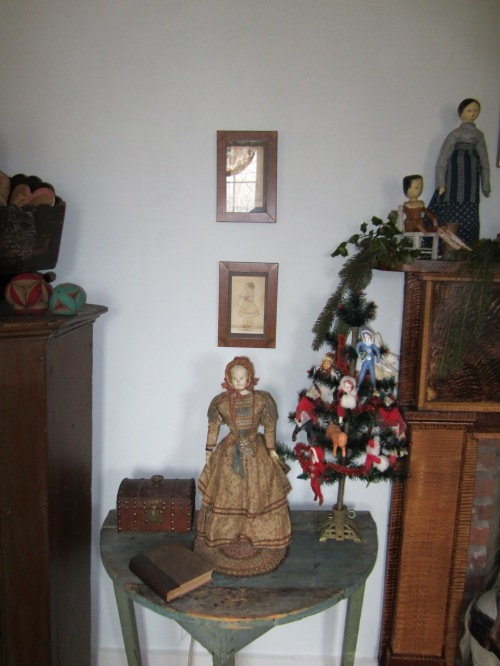 A French papier-mache doll stands beside a small feather tree filled with some of the spun cotton ornaments that I make.